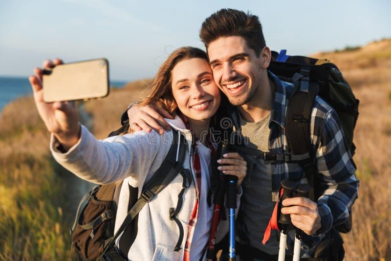 Exterior cariñoso joven feliz de los pares con la mochila en selfie de la toma de las vacaciones que acampa alternativas libres p imágenes de archivo libres de regalías