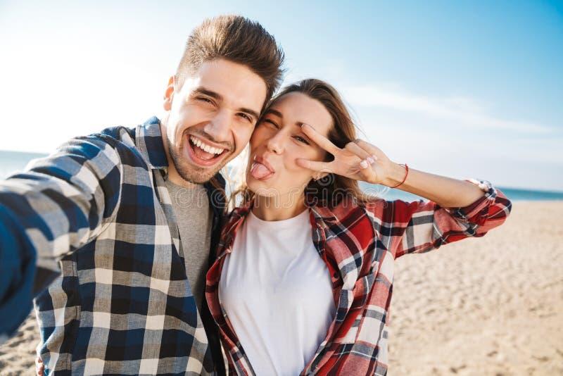 Exterior cariñoso joven feliz de los pares en selfie de la toma de las vacaciones que acampa alternativas libres por la cámara imágenes de archivo libres de regalías