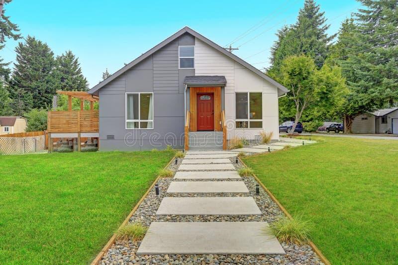Exterior cinzento e branco agradavelmente renovado da casa fotografia de stock royalty free