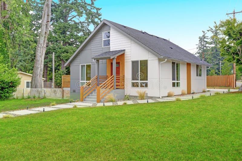 Exterior cinzento e branco agradavelmente renovado da casa imagens de stock royalty free