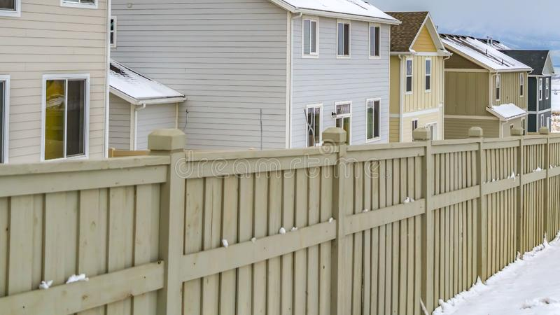 Exterior claro del panorama de hogares dentro de una cerca de madera contra un paisaje nevoso en invierno imágenes de archivo libres de regalías
