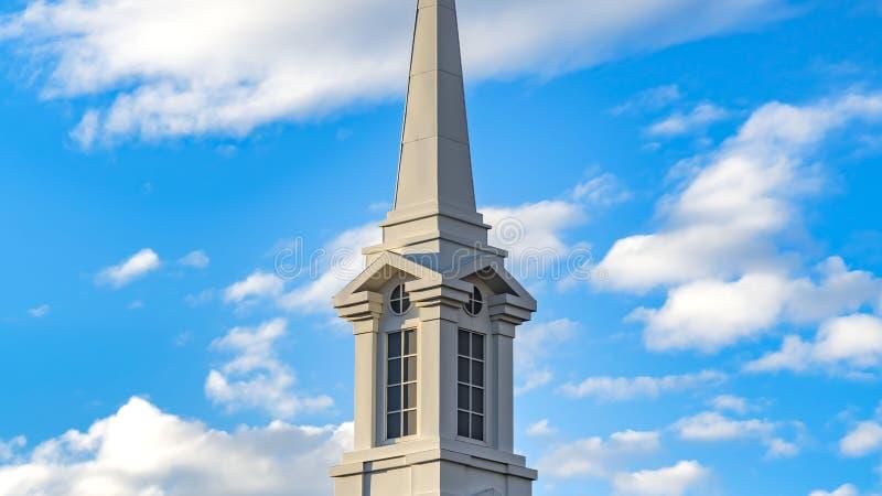 Exterior claro do panorama de uma igreja bonita com uma torre branca contra o céu azul nebuloso fotos de stock royalty free