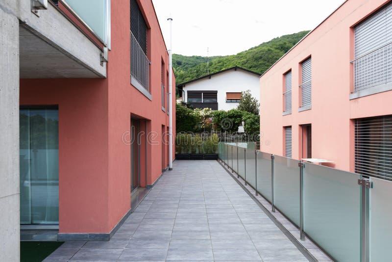 Exterior constructivo rojo con la terraza grande y el parapeto de cristal imágenes de archivo libres de regalías