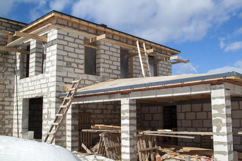 Exterior of a country house under construction with scaffolding and holders for gutters water drainage system of roof. Site on. Which the walls are built of gas royalty free stock photo
