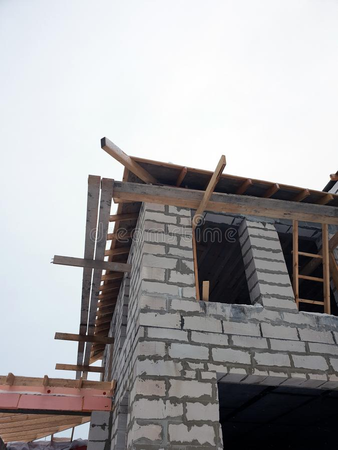 Exterior of a country house under construction. Site on which the walls are built of gas concrete blocks and ladder. Brick, cement, home, work, equipment royalty free stock photo
