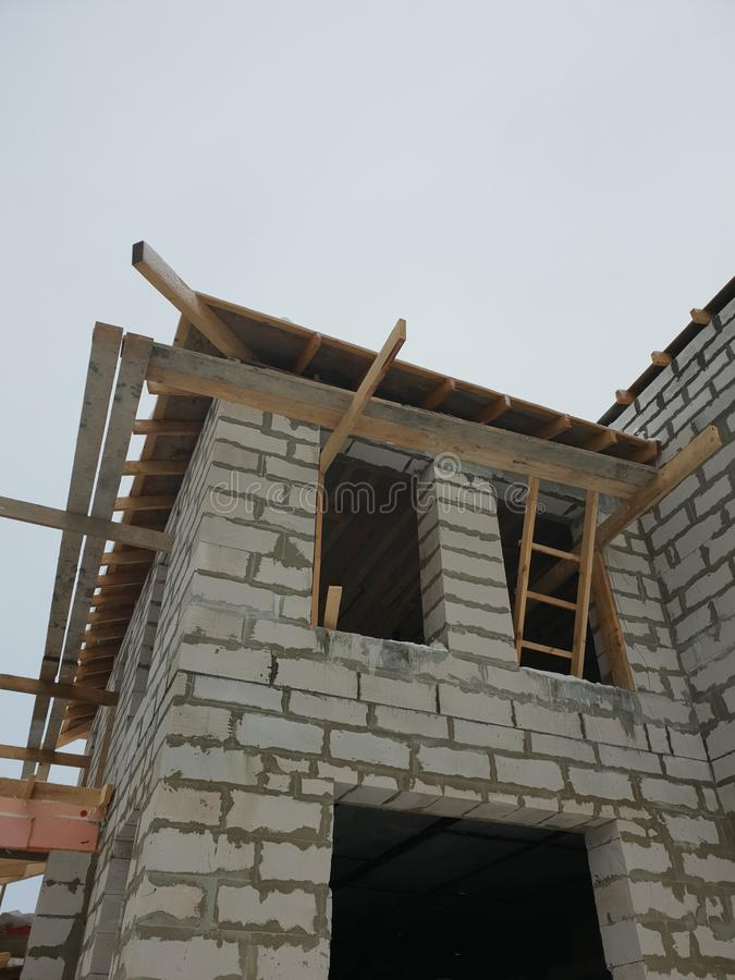 Exterior of a country house under construction. Site on which the walls are built of gas concrete blocks and ladder. Brick, cement, home, work, equipment royalty free stock image