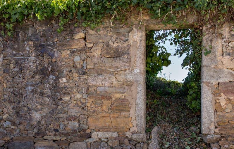 Exterior da construção de pedra arruinada antiga Casa abandonada velha com entrada e grama vazias Casa arruinada do tijolo com po fotografia de stock