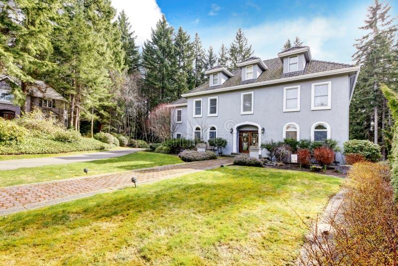 Exterior da HOME da grande casa clássica cinzenta com pinheiros. fotos de stock