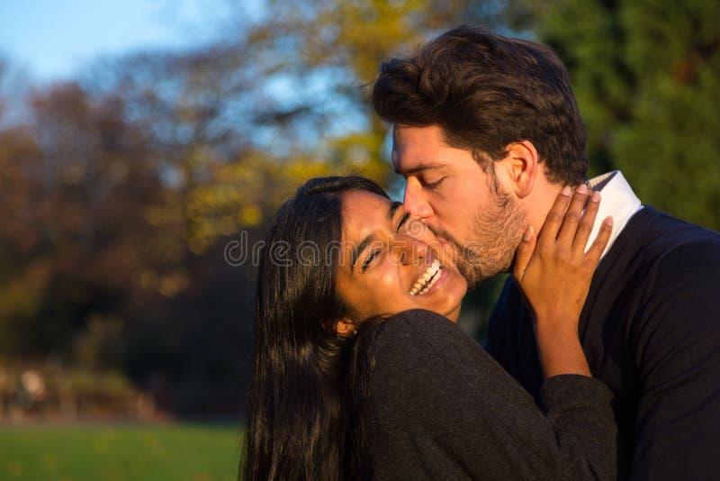 Exterior de abrazo y que se besa de los pares en parque imagen de archivo