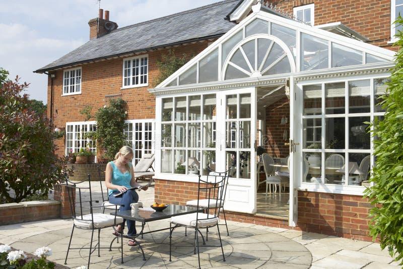 Exterior de la casa con el invernadero y el patio imagenes de archivo