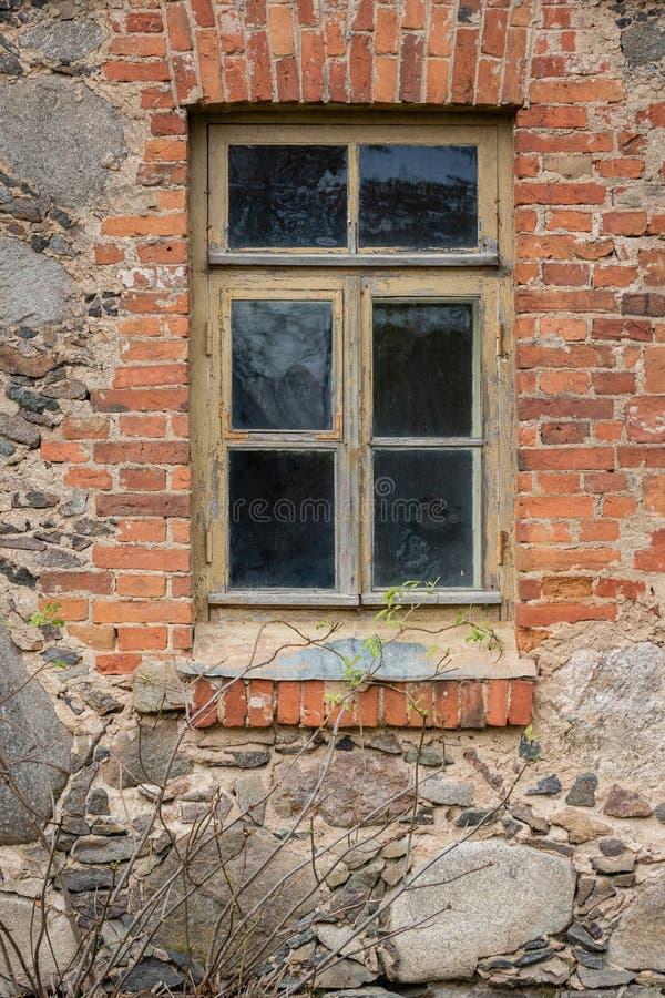 Exterior de una casa vieja de la piedra y del ladrillo con el marco de ventana del vintage foto de archivo