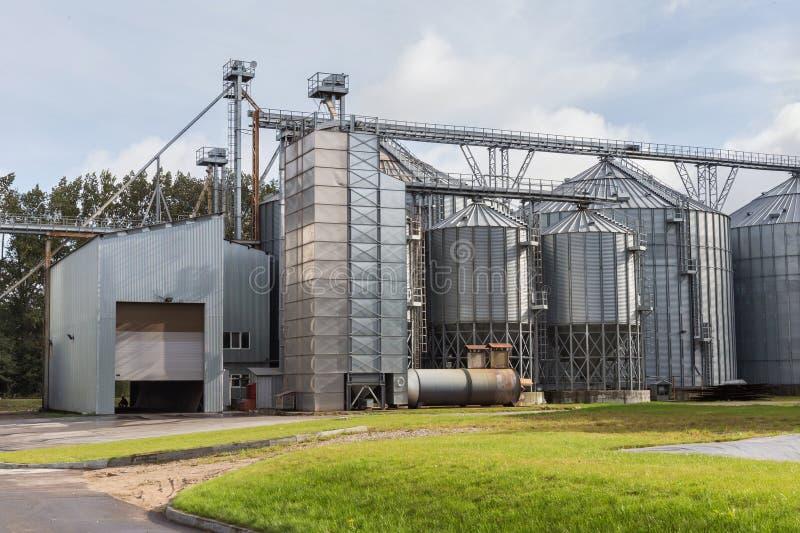 Exterior del edificio agrícola de Silo con los tanques de almacenamiento para la planta de tratamiento agrícola de las cosechas fotografía de archivo
