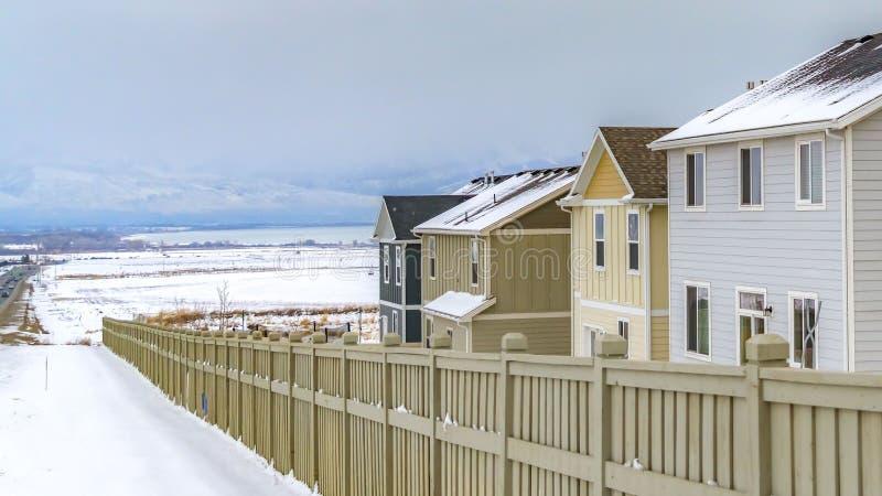 Exterior del panorama de hogares dentro de una cerca de madera contra un paisaje nevoso en invierno foto de archivo libre de regalías