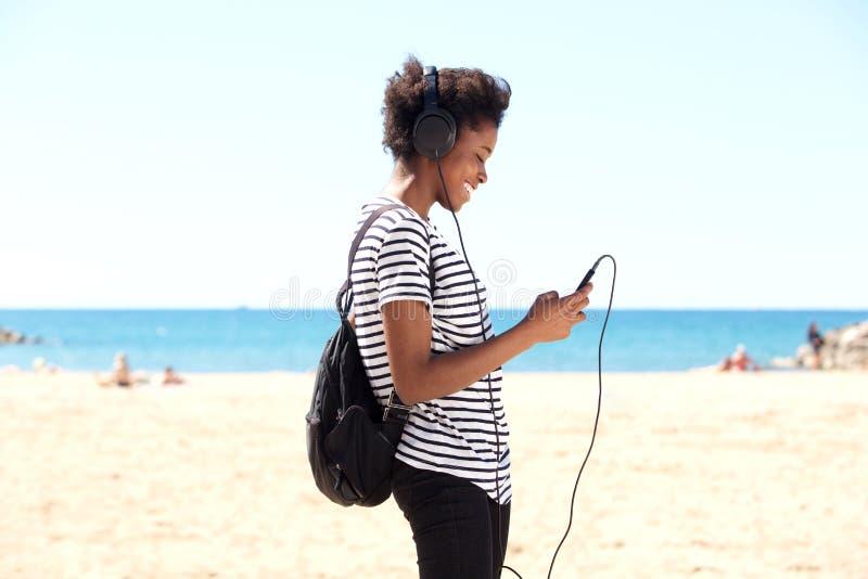 Exterior derecho de la mujer africana joven y el escuchar la música del teléfono elegante imagen de archivo libre de regalías