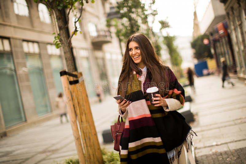 Exterior derecho de la mujer, café de consumición a ir sostener un mobi imágenes de archivo libres de regalías