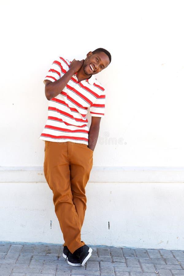 Exterior derecho y sonrisa del hombre africano joven feliz imagenes de archivo