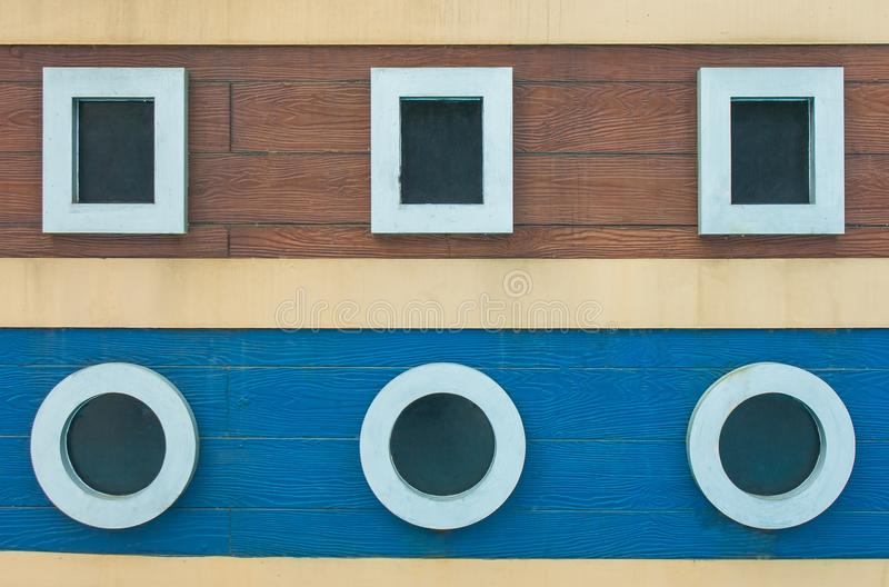 Exterior design of wall background buildings with square and circle shapes of window on vintage wooden background. royalty free stock photos