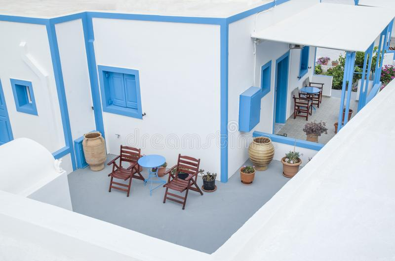 Exterior do hotel grego pequeno com tabelas, cadeiras e vasos fotografia de stock