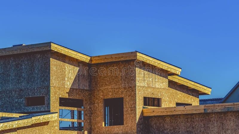 Exterior do quadro do panorama de uma casa sob a construção contra o céu azul claro em um dia ensolarado imagem de stock