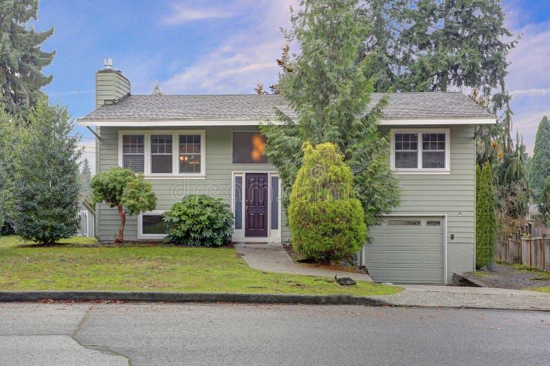 Exterior do renovado agradavelmente em casa com tapume verde e guarnição branca fotos de stock