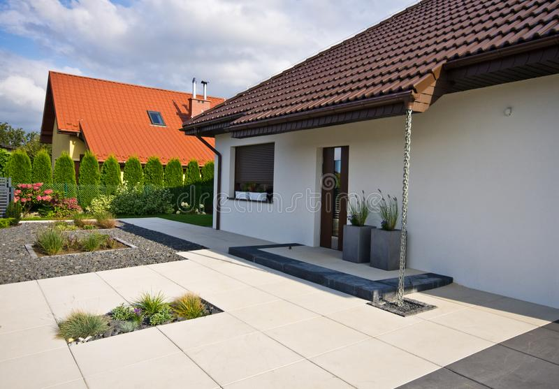 Exterior of a modern house with elegant architecture. The exterior of an elegant modern house with designer surroundings. Garden, lawn and plants arranged with stock photos