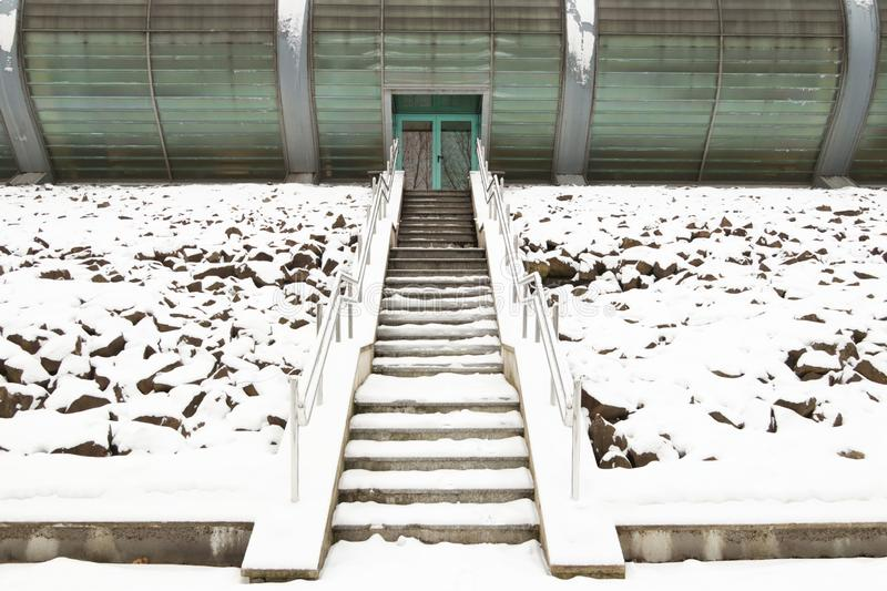 The exterior of the entrance to the modern building is a stone staircase with railings in the winter season. Modern architecture royalty free stock photo