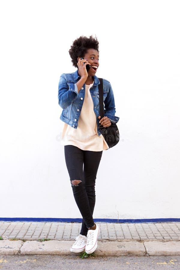 Exterior ereto da jovem mulher à moda e fala no telefone celular imagem de stock royalty free