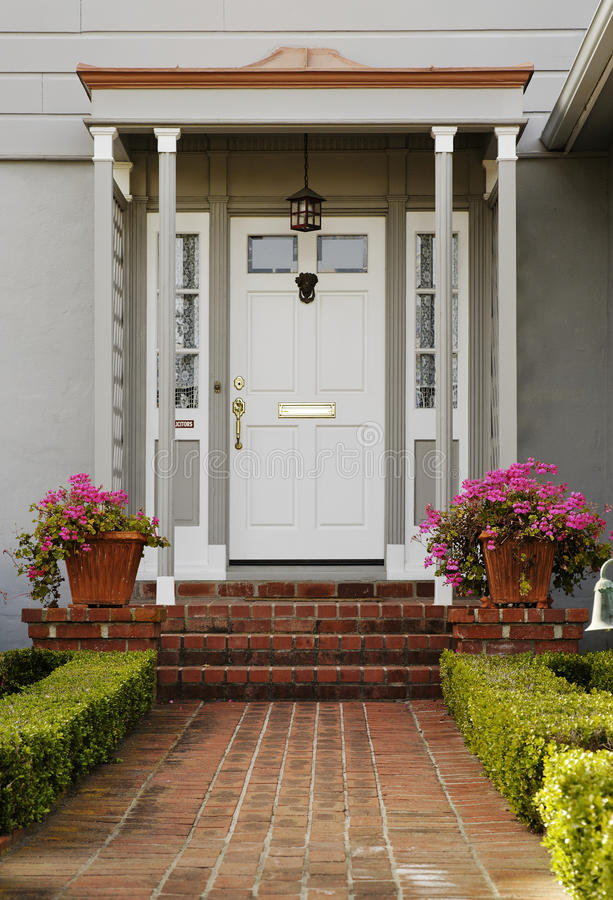 Exterior of a Front Door. A brick walkway and steps lead to the front door of a house. There is a covered, column supported porch. Vertical shot stock images