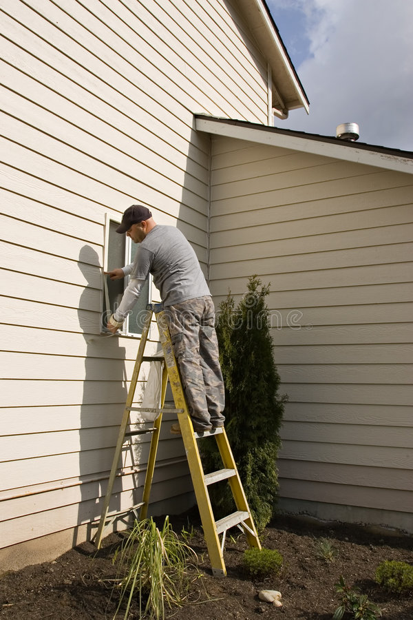 Exterior House Painting. Painter / Worker standing on a ladder while applying /masking tape to window in preparation for residential exterior house painting royalty free stock image