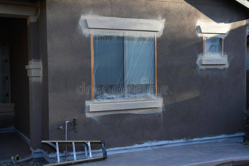 Exterior House Painting. Residential house / home being prepared for exterior painting with windows covered / masked with plastic and several ladders against royalty free stock images