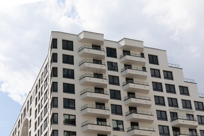 Exterior look of high modern new-built apartment house with beige facade, windows and balcony. Ground view at sky. Background royalty free stock images
