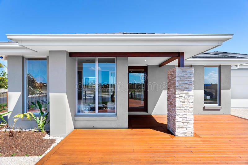 Exterior of a modern house with a wooden floor with blue sky royalty free stock image