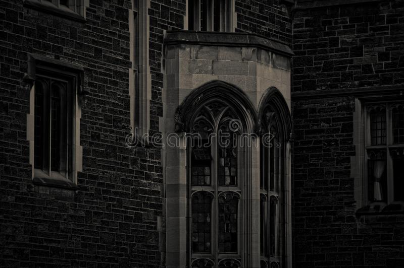 Exterior of an old gothic building with stone walls and bay window in the evening dusk.  royalty free stock image