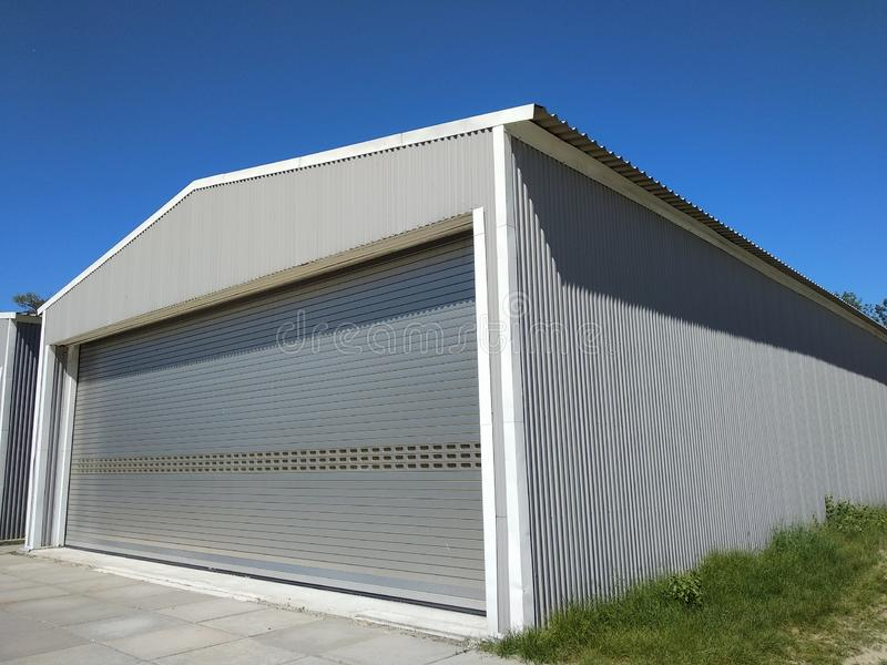Exterior of one metal hangar for manufacturing or storage. Side view garage with closed rolling doors with concrete blocked flow. royalty free stock photo