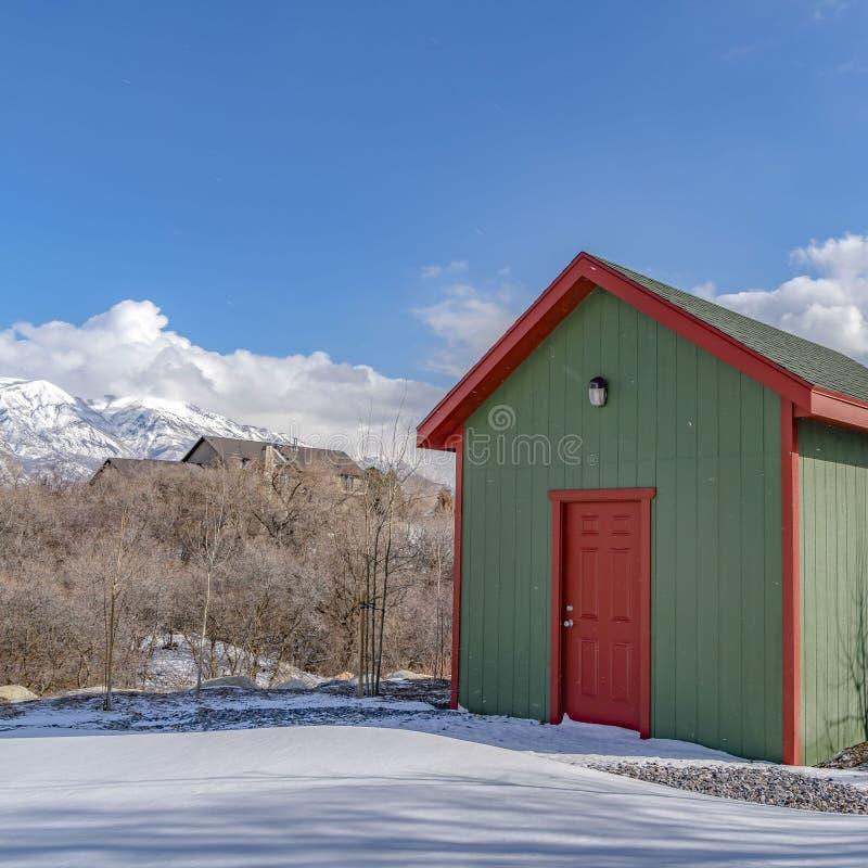 Exterior quadrado claro de uma vertente de madeira do armazenamento construída em uma terra coberto de neve no inverno imagem de stock royalty free