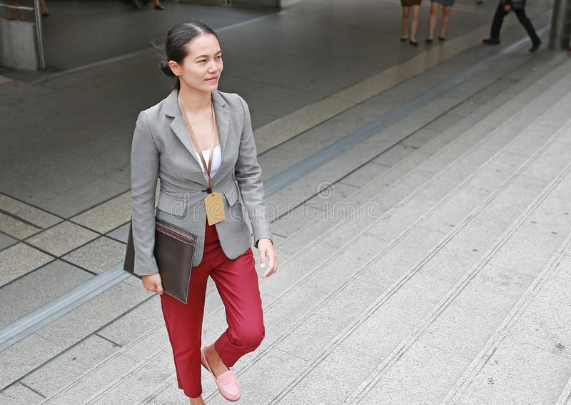 Exterior que camina joven hermoso de la mujer de negocios Oficinista asiático de la empresaria en distrito financiero céntrico foto de archivo