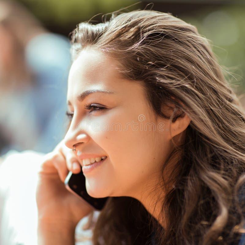 Exterior que se sienta hermoso de la mujer joven que tiene una conversación sobre su teléfono celular imagen de archivo libre de regalías