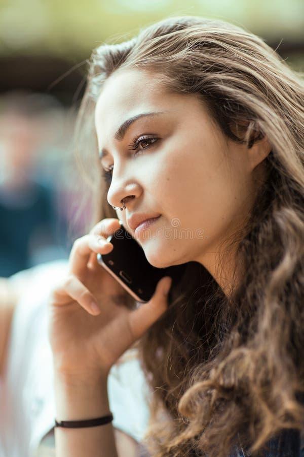 Exterior que se sienta hermoso de la mujer joven que tiene una conversación sobre su teléfono celular imagenes de archivo