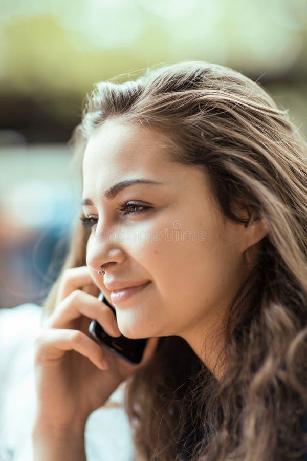 Exterior que se sienta hermoso de la mujer joven que tiene una conversación sobre su teléfono celular imagen de archivo