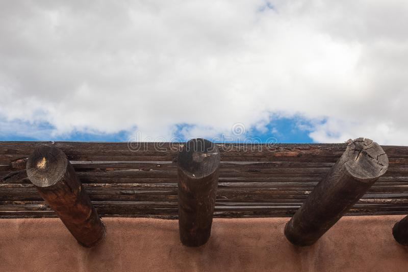 Exterior red adobe building with beams and wood sun screen slats, blue sky and clouds. Horizontal aspect stock images