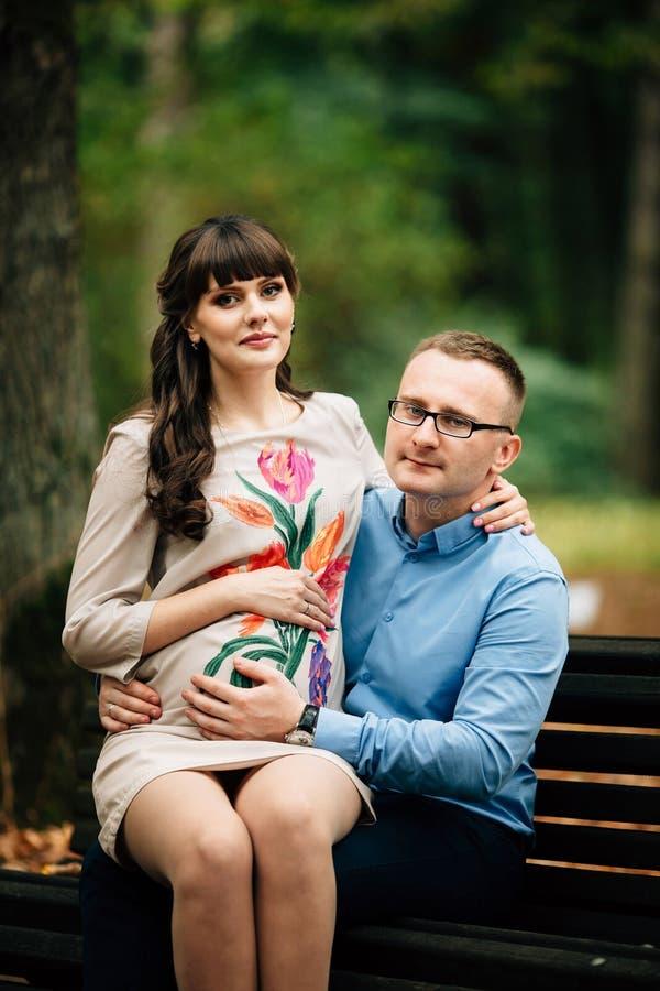 Exterior relajante de los pares embarazadas hermosos y felices en el parque del otoño que se sienta en banco imagen de archivo