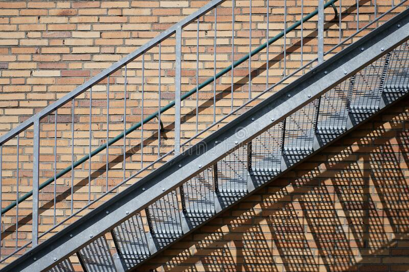 Exterior steel staircase on a red brick building wall with harsh shadow casting. Concept for construction and industry, structure and architecture, climbing stock image