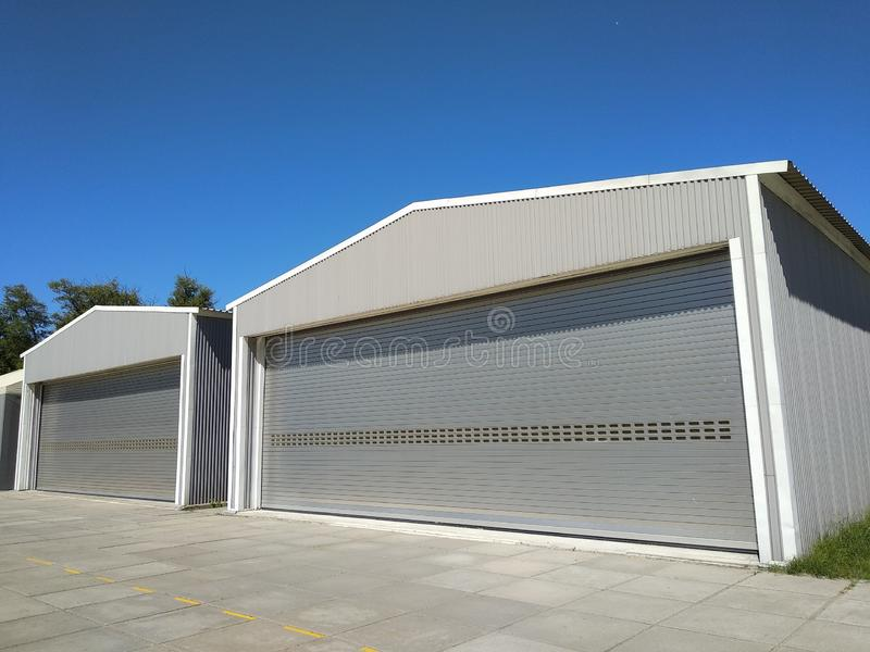 Exterior of two metal hangar for storage under blue sky. Side view of two garages with closed rolling doors with concrete blocked stock photos