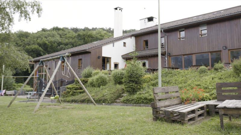 Exterior verde hermoso de una casa moderna en fondo gris del cielo acci?n Yarda con el área de la hierba verde y del patio, oscil foto de archivo