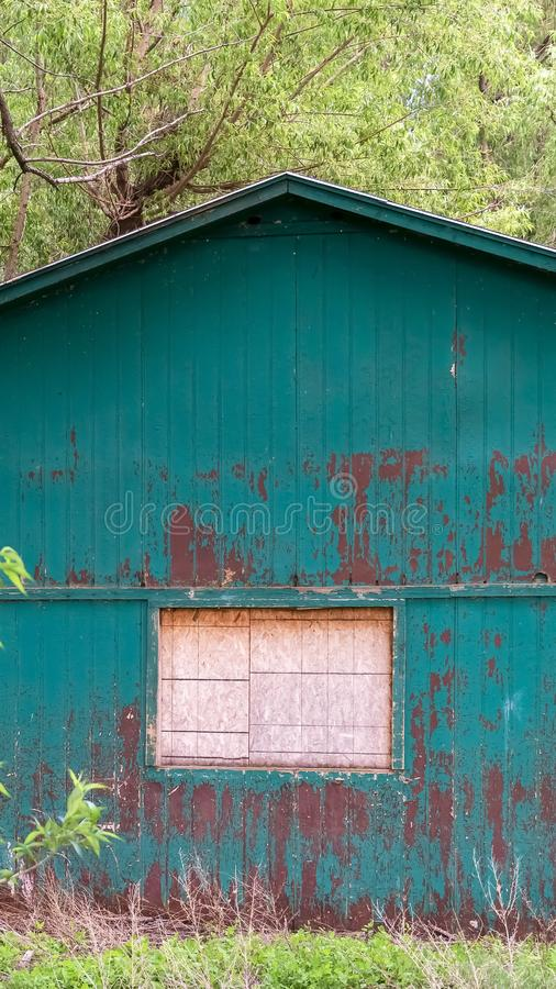 Exterior vertical del marco de la vertiente en el bosque con la ventana blanca y la peladura de la pintura verde en la pared foto de archivo