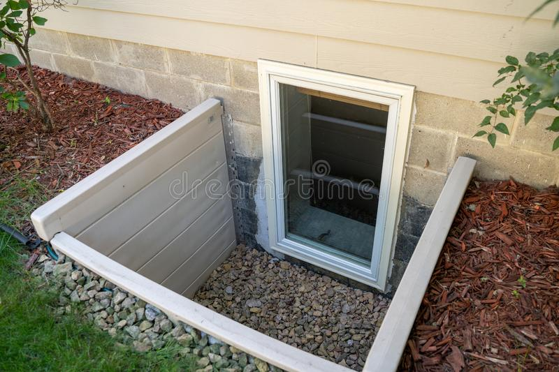 Exterior view of an egress window in a basement bedroom. These windows are required as part of the USA fire code for basement. Bedrooms royalty free stock photo