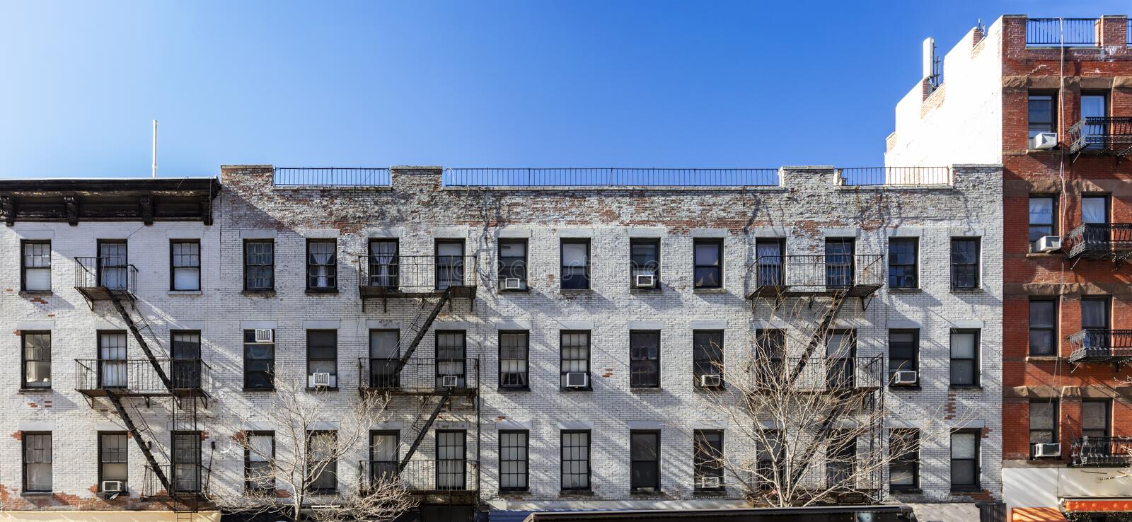 Exterior view of the facade of an old brick apartment buildings with windows and fire escapes in New York City stock image