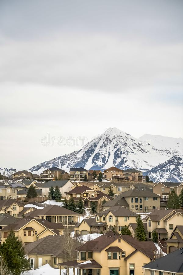 Exterior view of homes surrounded by fresh white snow and conifers in winter. A towering frosted mountain and cloudy sky can be seen in the background royalty free stock image