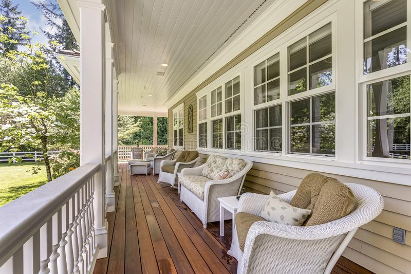Large country home with wrap-around deck. Exterior view of a large country residence with wrap-around deck and cozy sitting area royalty free stock images