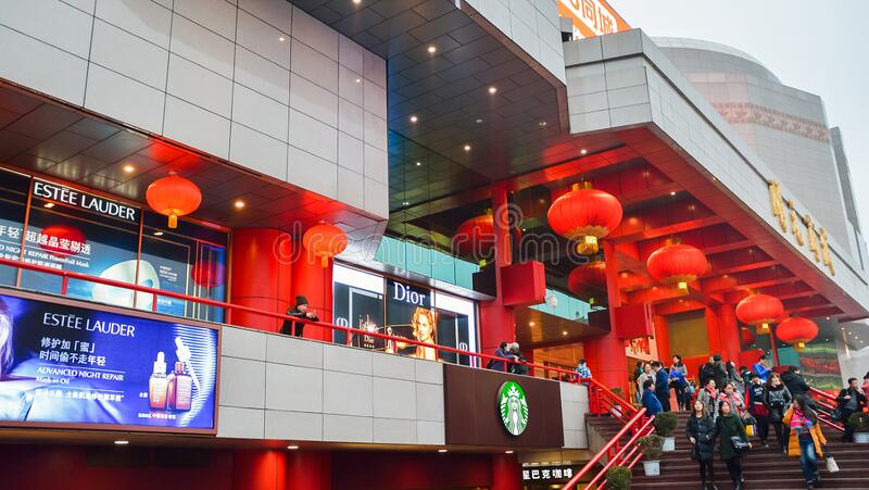 Exterior of shopping mall decorated with red lanterns and tourists on stairs. royalty free stock image